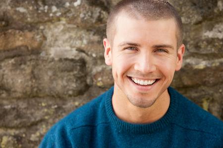 Atrakcyjny młody człowiek siedzi na zewnątrz. On uśmiecha się do kamery. Zdjęcie Seryjne