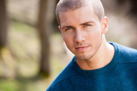 ojos verdes: Hombre joven atractivo que se sienta afuera. Él está mirando pensativo a la cámara. Foto de archivo