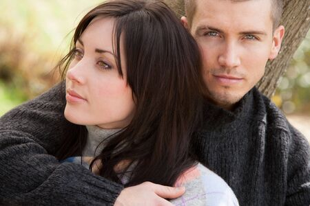 looking away from camera: Attractive young couple cuddling out doors. The man is looking at the camera whilst his partner is looking away to the side.