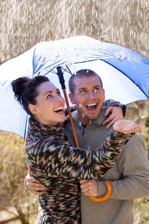 sotto la pioggia: Giovane coppia godendo la pioggia sotto un ombrello
