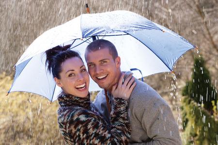 pareja abrazada: Pareja joven de risa en la lluvia bajo un paraguas Foto de archivo