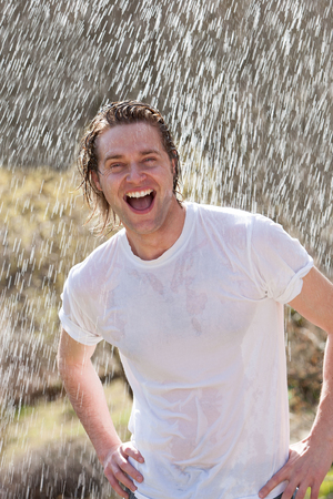An attractive young man having fun in the rain without an umbrella