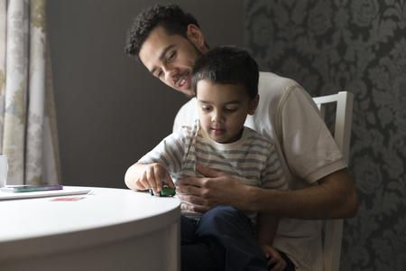 Kleine jongen zit op de knie van zijn vader, het spelen met een stuk speelgoed auto op de tafel.