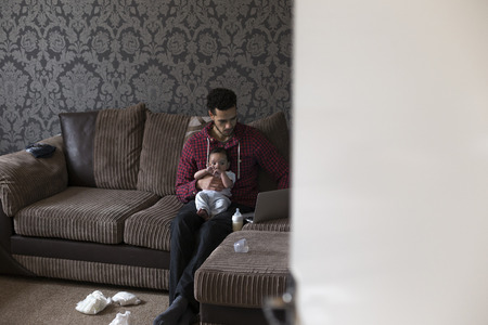 nappies: Young father sitting on his sofa at home with his baby son on his knee. He is working on a laptop and there are dirty nappies on the floor. Stock Photo