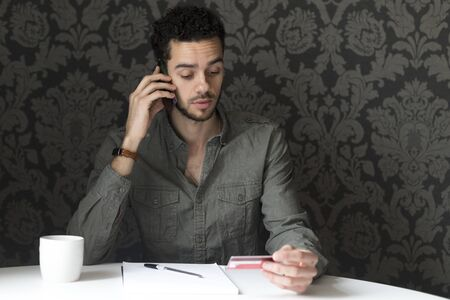 shopping card: Young man sitting at the table at home, using his smartphone and his bank card to pay bills over the phone. Stock Photo