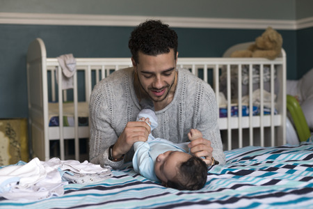 paternal: Young father is playing lovingly with his baby son, who is lying on his parents bed. Stock Photo