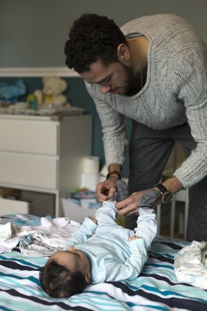 paternal: Young father is putting some socks on his baby son, who is lying on his parents bed. Stock Photo