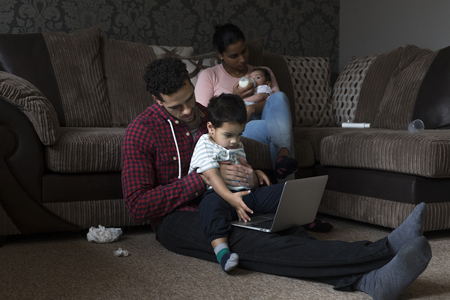 eldest: Family of four at home. The father is sitting on the floor with his eldest son using a laptop. The mother is sitting on the sofa behind them, feeding their baby a bottle of milk.