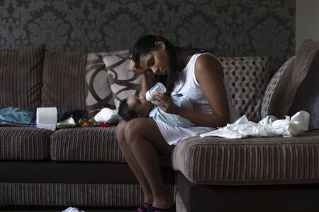 mess: Stressed young mother sitting on her sofa whilst feeding her baby son. She has her head in her hand and is surrounded by mess.