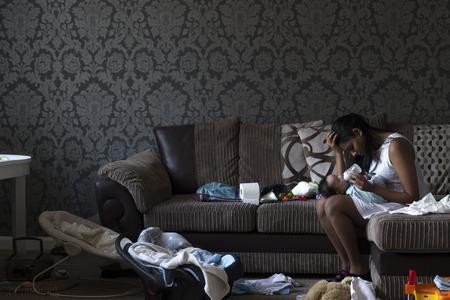 그녀의 아기가 아들을 먹이 동안 그녀의 소파에 앉아 스트레스 젊은 어머니. 그녀는 그녀의 손에 그녀의 머리를 가지고 엉망으로 둘러싸여 있습니다. 스톡 콘텐츠