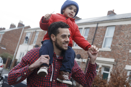 outside house: Young father carrying his son on his shoulders as he walks down the street Stock Photo