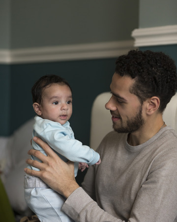 paternal: Young father sitting on his bed, holding his baby son.