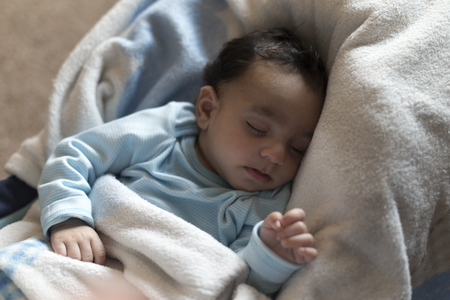 0 3 months: cute, baby boy is fast asleep in his car seat. He is wrapped up in a fluffy blanket with a teddy beside him. Stock Photo