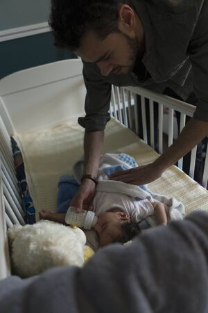 nodding: Young father feeding his son a bottle. He is lying in his cot, nodding off to sleep. Stock Photo