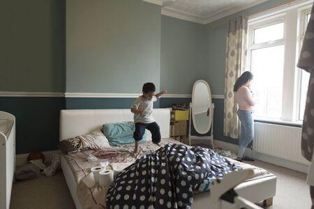 habitacion desordenada: El niño pequeño está saltando en la cama de su madre, que está de pie junto a la ventana con su hijo bebé en sus brazos.