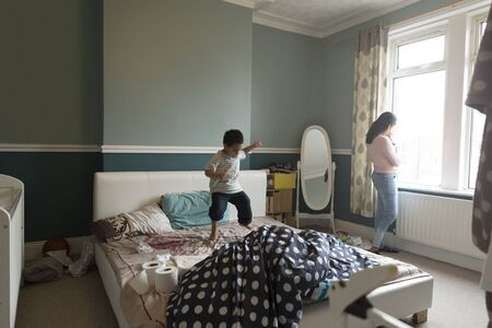 0 3 months: Little boy is jumping on his mothers bed, who is standing by the window with her baby son in her arms.