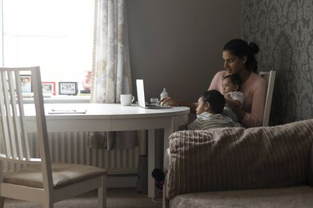 eldest: Young mother keeping her children entertained by showing them something on her laptop. She is holding her baby son and the eldest is leaning on her leg whilst looking at the screen.