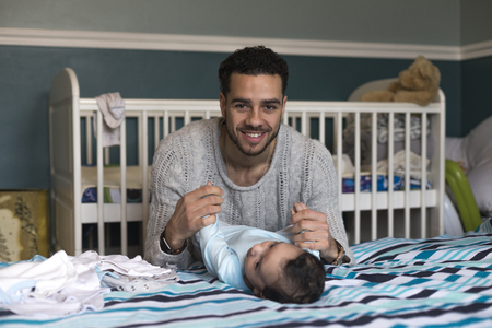 paternal: Young father is smiling at the camera whilst playing with his baby son, who is lying on his parents bed. Stock Photo