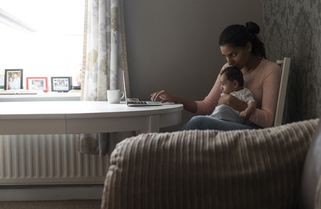0 3 months: Young mother sitting at the table at home, using a laptop and holding her baby son.