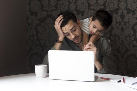 niño trepando: El niño pequeño está subiendo en su padre, tratando de ayudarlo con su banca por Internet. Están sentados detrás de un ordenador portátil en casa.