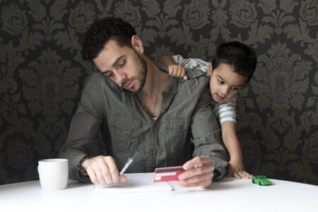 Little boy is climbing on his dad, playing with his toy car. His dad is trying to make bill payments through the phone.