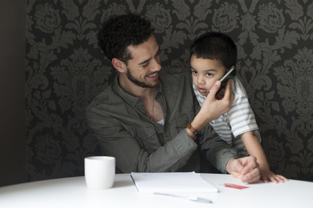 imitating: Young father is laughing as his son copies him. He is holding the phone to his sons ear, who is pretending to talk to someone.