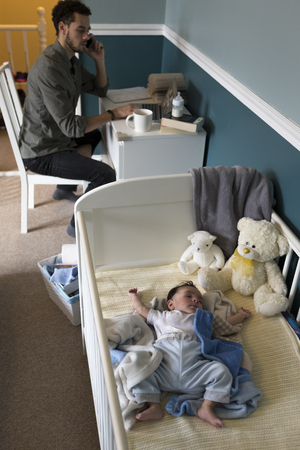 home working: Young father working from home whilst his baby son is sleeping in his cot. Stock Photo