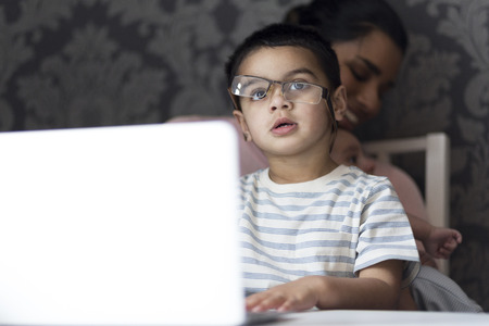 Little boy is imitating his mother by attempting to put her glasses on and typing on the laptop. His mother is in the background, feeding her baby son.