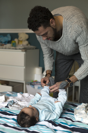 single family: Young father is putting some socks on his baby son, who is lying on his parents bed. Stock Photo
