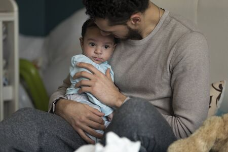 cuddles: Young father having cuddles with his baby. They are sitting on dads bed.
