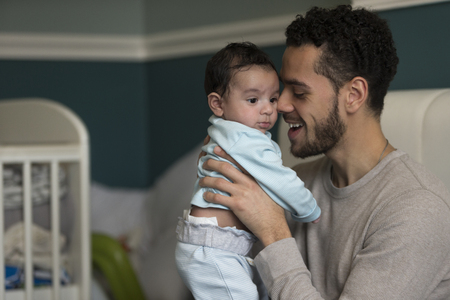paternal: Young father sitting on his bed, holding his baby son. He has his nose pressed to his sons cheek. Stock Photo