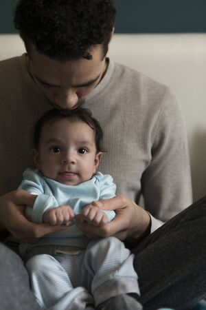 paternal: Young father sitting with his baby son in his lap. He is holding his hands and kissing him on his head. The baby is looking at the camera. Stock Photo