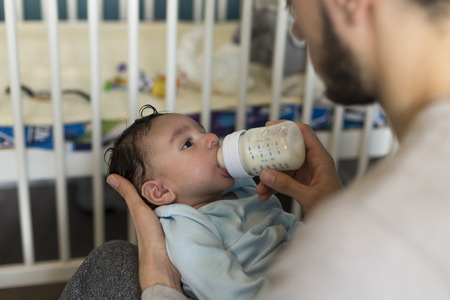 paternal: Young father is sitting with his baby son in his lap. He is feeding him a bottle of milk.
