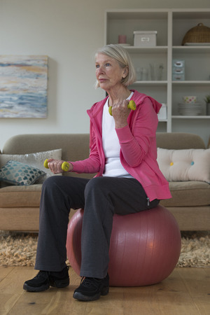 Senior lady sitting on a gym ball in her home whilst using dumbbells.