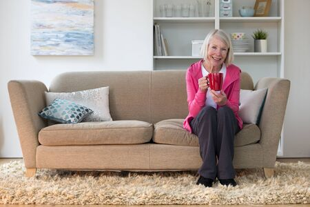 one senior woman only: Senior lady sitting at home on her sofa in the living room. She is smiling at the camera and holding a cup of tea.