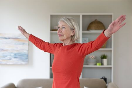 one senior woman only: Senior woman exercising in her living room. She has her arms outstretched.