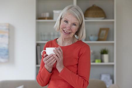 Portrait einer älteren Frau. Sie lächelt und schaut in die Kamera mit einer Tasse Tee in der Hand.