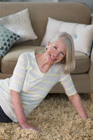one senior woman only: Senior woman smiling for the camera whilst doing pilates at home.