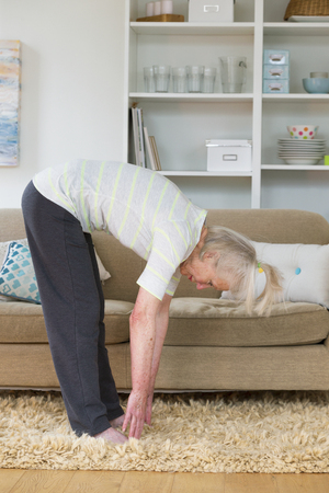 touching toes: Senior woman doing exercise in her home.