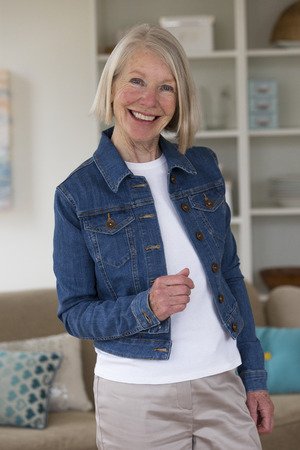 one senior woman only: Portrait of a senior woman in her home.She is wearing a denim jacket. Stock Photo