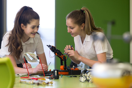 Two female students are working together in school to build a functioning robotic arm. Stockfoto