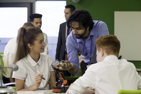 teacher student: Students in school are building a robotic arm. The teacher is discussing the design with them. Stock Photo