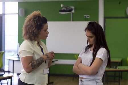 women talking: Teenage student being told off by her teacher at school.