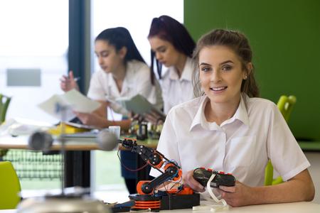 Adolescent meisje in een design en technologie les. Ze lacht naar de camera met een robotarm die ze Infront van haar bouwt.