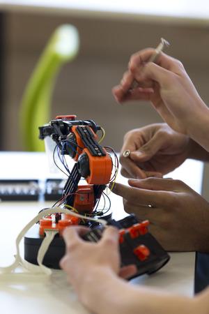 Close-up shot van de studenten handen werken aan een robotarm.