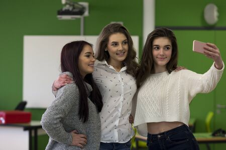 school friends: Three female students taking a selfie together on a smartphone in a classroom. Stock Photo