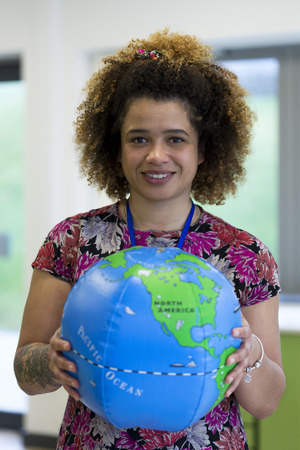 blow up: Teacher in a classroom holding a blow up globe to the camera.