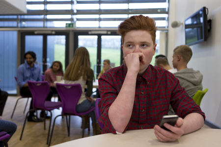 sixth form: Stressed schoolboy sitting away from people at school. He has a smartphone in his hand and is looking away with his hand to his face. Stock Photo