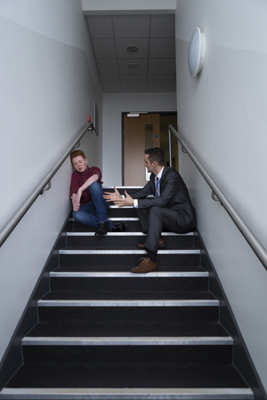 Male student is sitting on the stairs in his school, with his teacher next to him. He is telling him off for his behaviour.