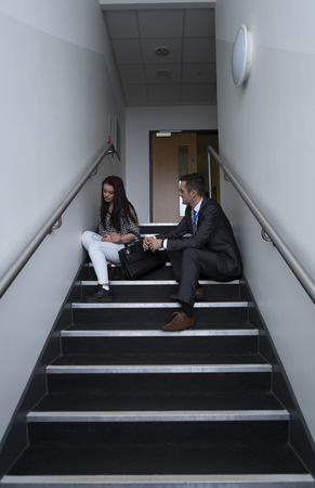sixth form: Female student is sitting on the stairs in her school, with her teacher next to her. He is telling her off for her behaviour.